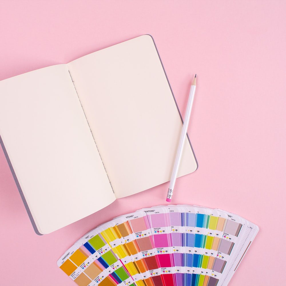 A pencil, notebook and color-wheel placed on a pink surface