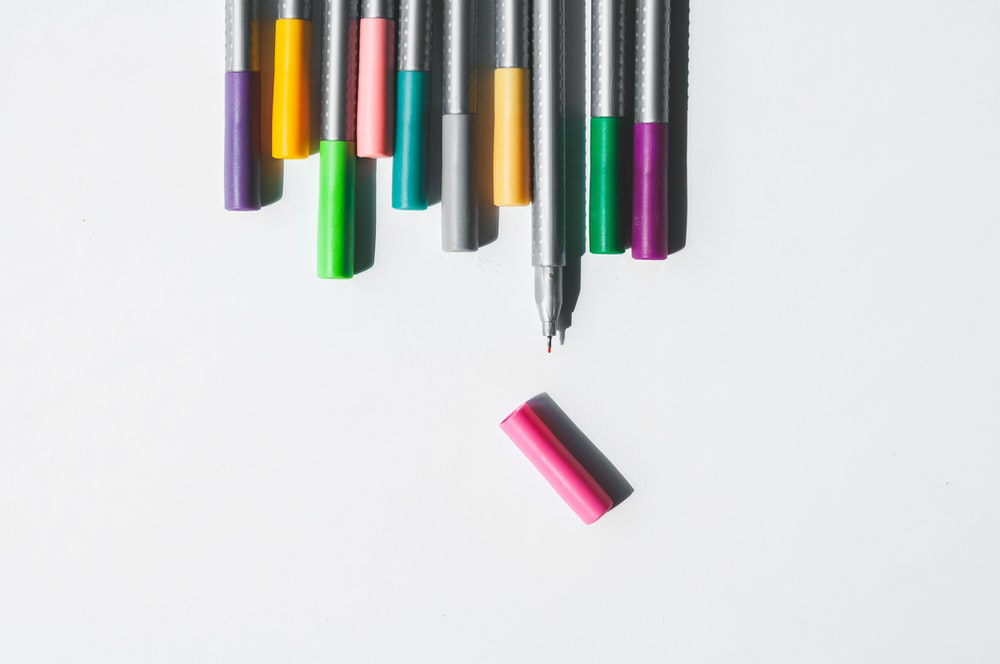 Assorted color pens on a white background