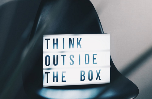A card on a chair that says, 'think outside the box.'