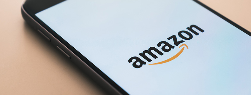 A phone with the Amazon app on it, displaying the logo on its screen