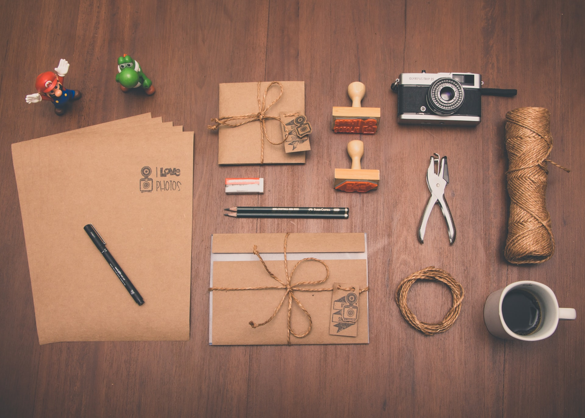 Brown papers, file, and camera lying on a wooden table